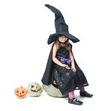 Little witch sits on a pumpkin Stock Images