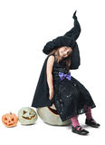 Little witch sits on a pumpkin Stock Photos