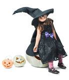Little witch sits on a pumpkin Stock Photo
