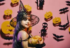 Little witch wearing black hat. Halloween party and decorations concept. Girl with smiling face on pink background with bats and pumpkins decor. Kid in spooky royalty free stock photography