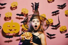 Little witch wearing black hat. Halloween party. Kid in spooky witches costume. Holds carved pumpkin. Halloween party and decorations concept stock image
