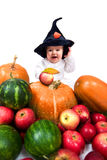 Little wizard. Cute little boy in the wizard hat with lots of vegetables Royalty Free Stock Images