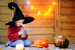 Little wizard looking on candle. Halloween concept Stock Photo