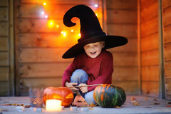 Little wizard playing with halloween pumpkins Stock Photo