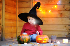 Little wizard playing with halloween pumpkins Royalty Free Stock Image