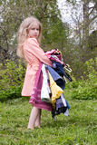 Little woman of fashion. Little girl standing with heap of dresses in her hands Stock Image