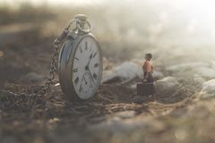 Little woman looks amazed at the big clock stock images