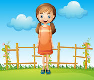 A little woman standing near the wooden fence Stock Photos