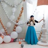 A little woman under big table lamp. Beautiful young blonde in blue skirt and hat. Fabulous setting, giant size. A little woman under a big table lamp. Beautiful Stock Photography