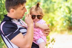 Amazing little girl is playing with sunglasses with her father royalty free stock photography
