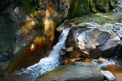 Little wondrous waterfall among the rocks in mountain forest Stock Photo