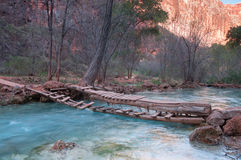 Little wooden bridge over mountain river Stock Photo