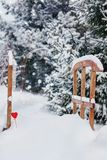 Little wooden bridge under the snow decorated with read heart in the blurred winter pine trees alley with falling snow stock photos