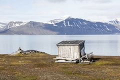 Little wooden fisherman`s hut lies in a fjord in Spitzbergen. Norway Royalty Free Stock Photography