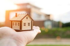 Little house in the child hand. Little wooden house in the child hand at sunset, symbol of movement and home. Selective focus on house stock image