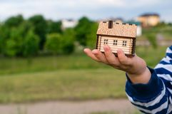 Little house in the child hand. Little wooden house in the child hand, symbol of movement and home. Selective focus on house royalty free stock photos
