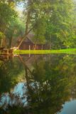 Little wooden house near water in forest. Sunrise time stock photos