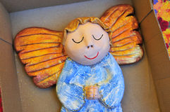 Little wooden painted angel figure sleeping in box Royalty Free Stock Photo