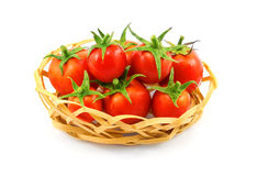 Little wooden wicker basket with red tomatoes isolated on white Stock Photos