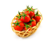 Little wooden wicker basket with red tomatoes isolated on white Royalty Free Stock Photos