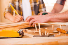 Little woodworker creating his dream. Close-up of young male carpenter teaching his son to work with wood in his workshop Stock Photo