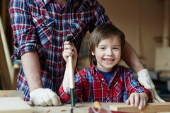 Little woodworker. Happy boy with hammer looking at camera Stock Photo