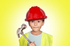 Little worker girl. Beautiful four years girl dressed like a worker with a hammer in the hands making faces. Studio shot. Yellow background Royalty Free Stock Images