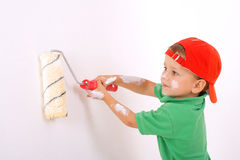 Little worker with paintroller. On white wall Royalty Free Stock Image