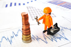 A little worker at a pyramid of coins. Against financial reports Royalty Free Stock Images
