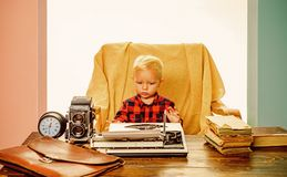 Little writer work on book at desk. Boy writer type on vintage typewriter in office.  royalty free stock photography