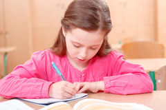 Little writing girl during classes Stock Photography