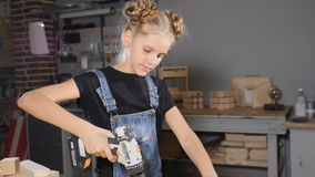 Little 10 year-old girl and a drill in hands. Slow motion. Young pretty girl builder is holding drill in her hands. Turning on, smiling, building conception stock video