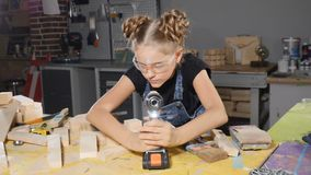 Little 10 year-old girl and a drill in hands. Slow motion. Young pretty girl builder is holding drill in her hands. Turning on, smiling, building conception stock footage