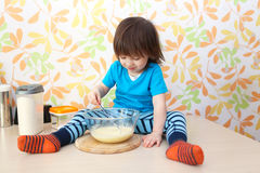 Little 2 years boy cooks sitting on a table at home kitchen Stock Photos