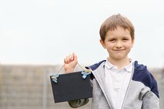 Little 7 years boy holding a empty blackboard Stock Images