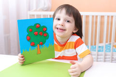 Little 3 years boy with long hair with crafts from plasticine an Royalty Free Stock Photos