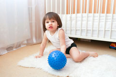 Little 2 years boy plays with fitness ball indoors Royalty Free Stock Photos