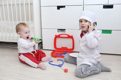 Little 4 years brother and 10 months sister play doctor Stock Photos
