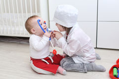 Little 4 years brother and 10 months sister play doctor at home Stock Photos