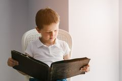 Little 7 years old boy browsing old photo album. Royalty Free Stock Image