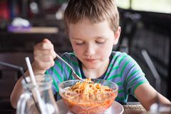 Little 7 years old boy child eating spaghetti bolognese Stock Photo