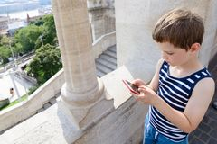 Little 7 years old boy playing mobile games on smartphone Stock Photography