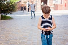 Little 7 years old boy playing mobile games on smartphone Royalty Free Stock Photo