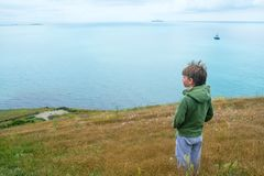 Little 6 years old boy stands on top of mountains and looking out to the sea. Summer evening in the mountains Royalty Free Stock Photo