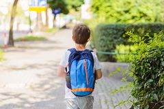 Little 7 years schoolboy going to school. Dressed in white t shirt and shorts. Blue backpack stock image