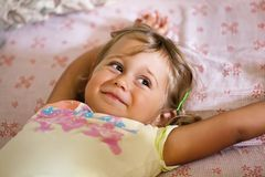 Little smiling girl lying on the bed stock photo
