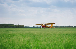 Little yellow airplane on field Stock Image