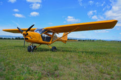 Little yellow airplane on green grass field Stock Photos