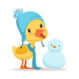Little yellow duck chick wearing blue knitted hat playing with snowman, cute emoji character vector Illustration Stock Image