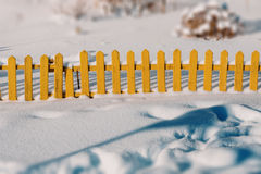 Little yellow fence. Is buried in fresh snow Stock Image